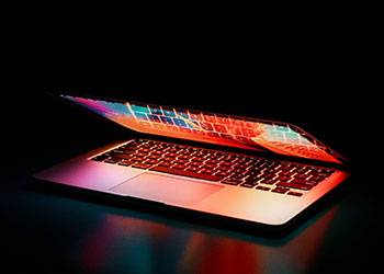 halb geöffneter Laptop im Dunkeln mit bunten Farben
