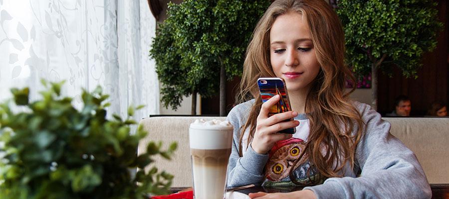 Mädchen mit iPhone und Kaffee