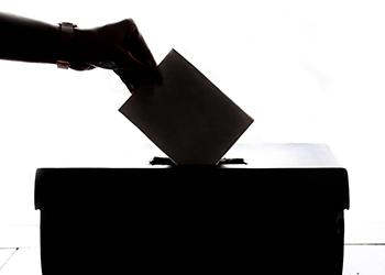 Person wirft Zettel in Box