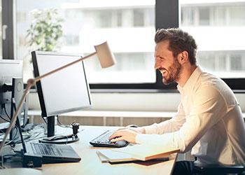 lächelnder Mann sitzt vor Computer