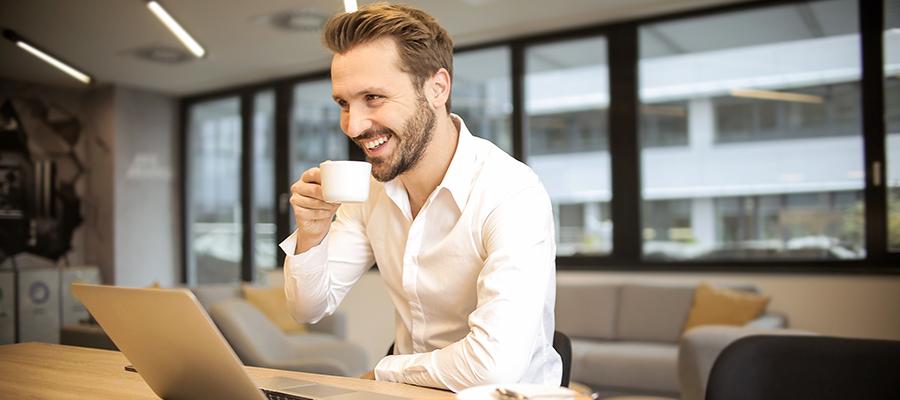Mann sitzt mit Kaffee vor Laptop