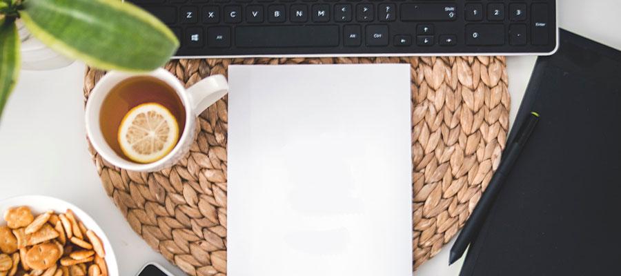 Schreibtischsituation mit Papier, Laptop und Teetasse