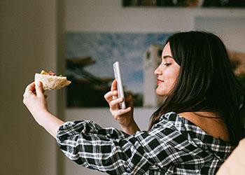 Mädchen fotografiert Pizza mit Smartphone